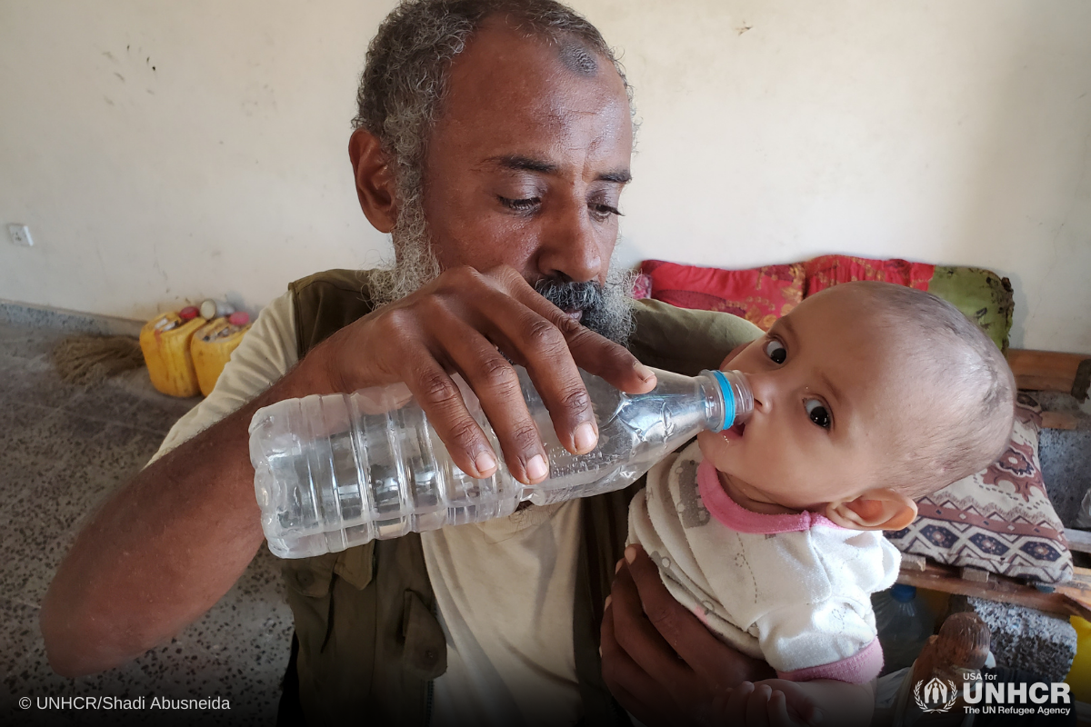 Sameer gives water to his boy inside a collective center for displaced people in Hudaydah, Yemen
